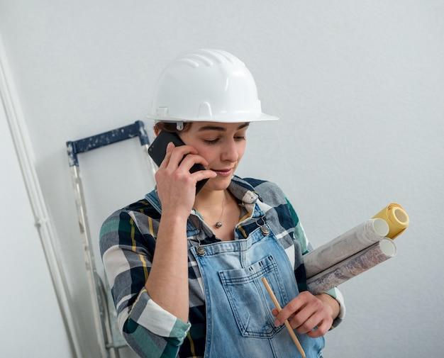 Junge ingenieurfrau mit schutzhelm sprechend am telefon Premium Fotos