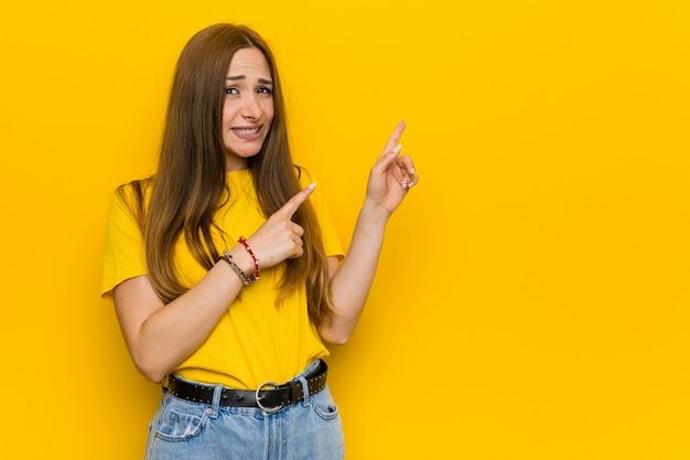 Junge ingwerrothaarigefrau entsetzte das zeigen mit den zeigefingern auf einen kopienraum. Premium Fotos