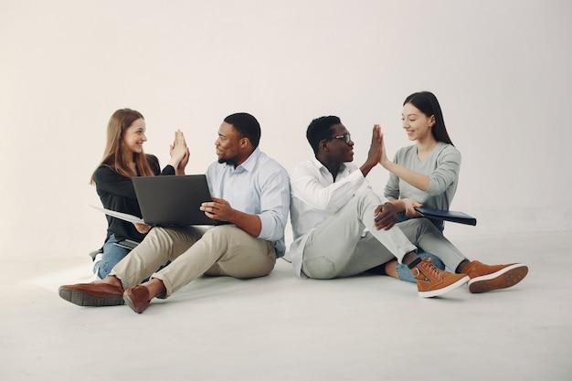 Junge internationale leute, die zusammenarbeiten und den laptop benutzen Kostenlose Fotos