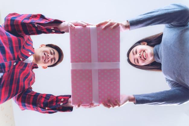 Junge jugendfrau und gutaussehender mann, die großes geschenk hält Kostenlose Fotos