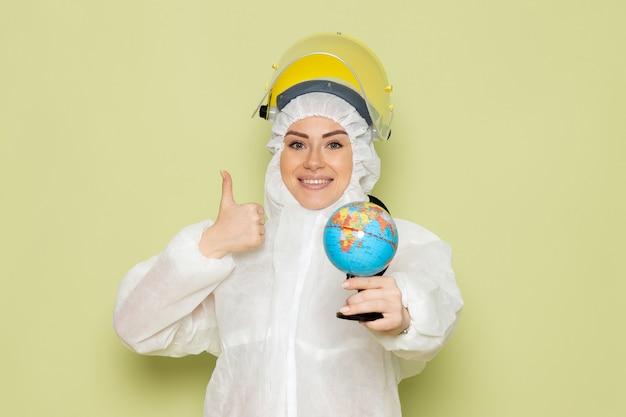 Junge junge frau der vorderansicht im weißen sonderanzug und im gelben helm, der kleinen globus mit leichtem lächeln auf der chemie der grünfläche hält Kostenlose Fotos