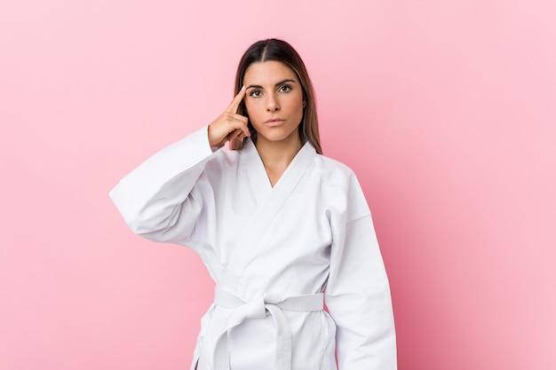 Junge karatefrau, die tempel mit finger zeigt, denkend, konzentrierte sich auf eine aufgabe. Premium Fotos
