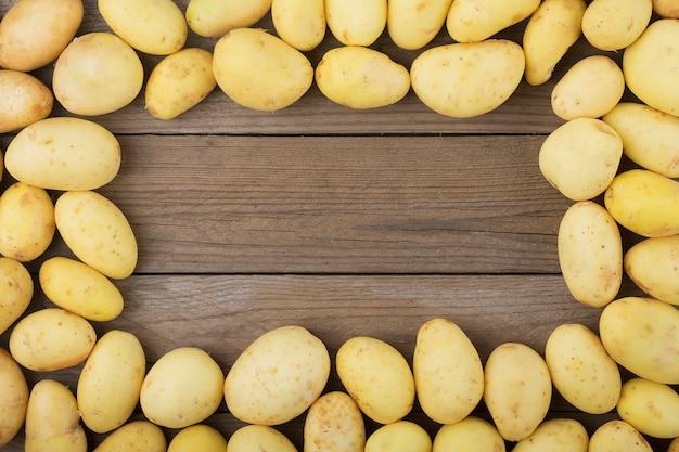 Junge kartoffeln auf holztisch. rustikaler stil. ansicht von oben. flach liegen. Premium Fotos