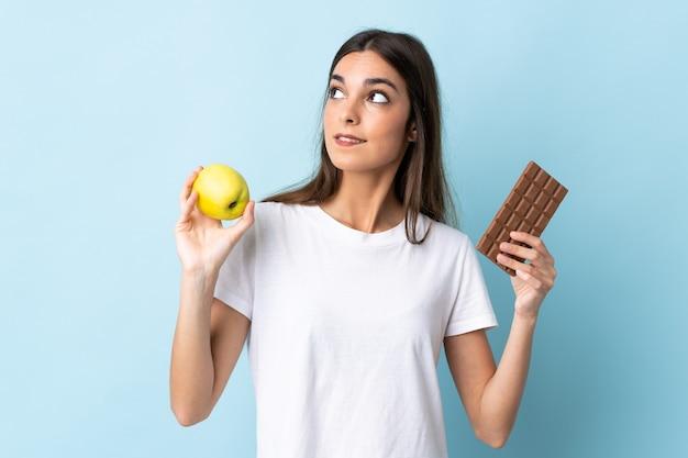 Junge kaukasische frau auf blau, die zweifel hat, während sie eine schokoladentafel in einer hand nimmt Premium Fotos