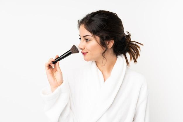 Junge kaukasische frau auf weißer wand, die make-up-pinsel hält Premium Fotos