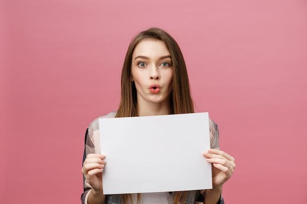 Junge kaukasische frau, die blatt des leeren papiers hält Premium Fotos