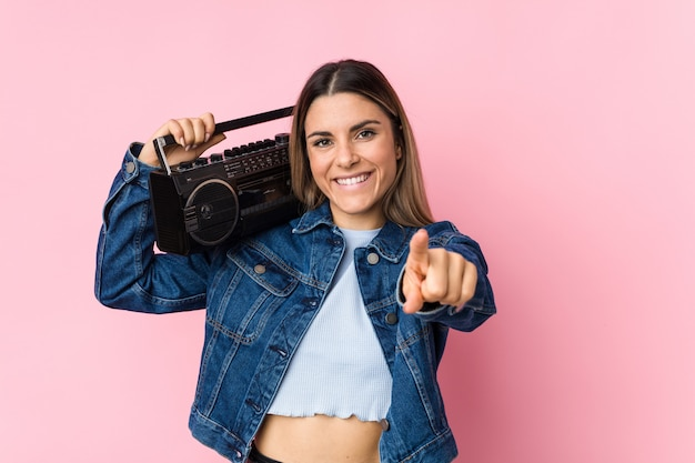 Junge kaukasische frau, die ein freundliches lächeln des guettoblasters zeigt auf front hält. Premium Fotos