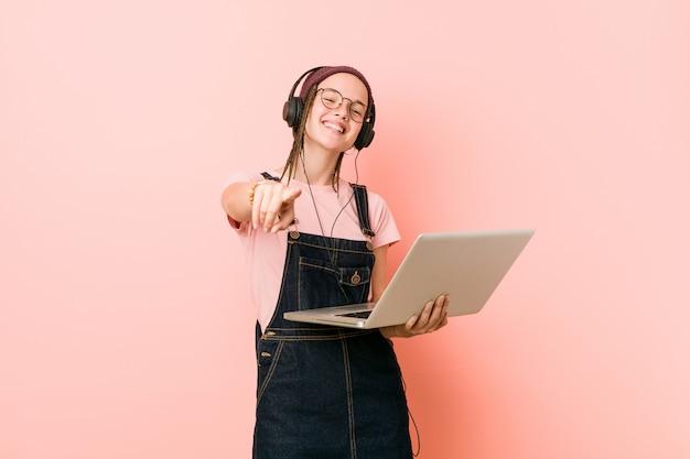 Junge kaukasische frau, die ein freundliches lächeln des laptops zeigt auf front hält. Premium Fotos