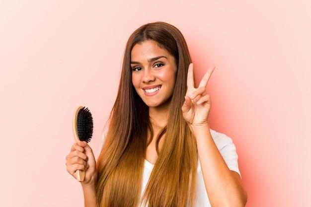 Junge kaukasische frau, die eine haarbürste zeigt siegeszeichen anhält und breit lächelt. Premium Fotos