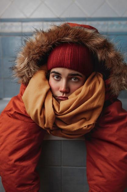 Junge kaukasische frau, die einen orangefarbenen mantel, einen gelben schal und eine rote wintermütze trägt, ist gelehnt und ruht in einer badewanne in einem badezimmer mit blauen fliesen und einem neutralen ausdruck. Premium Fotos