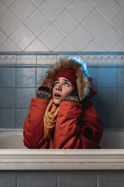 Junge kaukasische frau, die einen orangefarbenen mantel, einen gelben schal und eine rote wintermütze trägt, sitzt in einer badewanne in einem badezimmer mit blauen fliesen und hält ihren kapuzenpulli mit winterhandschuhen in den händen. Premium Fotos