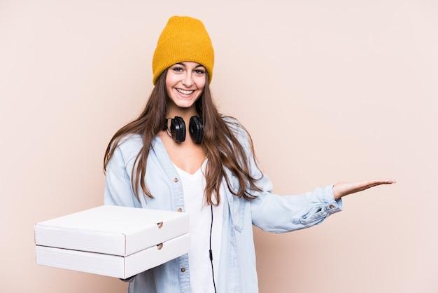 Junge kaukasische frau, die pizzen lokalisiert hält, die einen kopienraum auf handfläche zeigen und eine andere hand auf taille halten. Premium Fotos