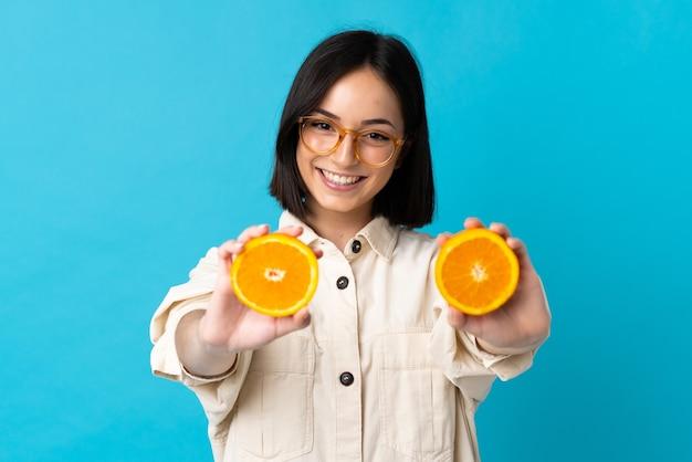 Junge kaukasische frau lokalisiert auf blau, das eine orange hält Premium Fotos
