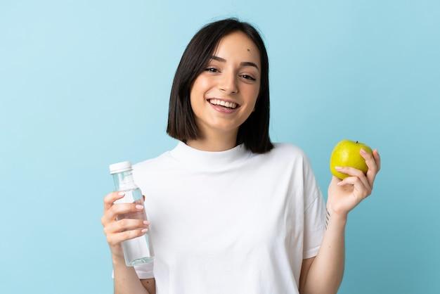 Junge kaukasische frau lokalisiert auf blau mit einem apfel und mit einer flasche wasser Premium Fotos