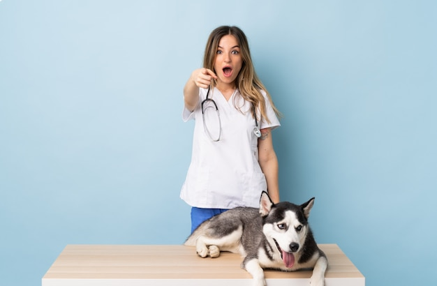 Junge kaukasische frau mit hund über isolierter wand Premium Fotos