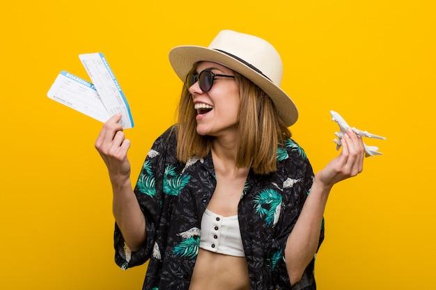 Junge kaukasische frau, welche die flugtickets sehr glücklich hält. Premium Fotos