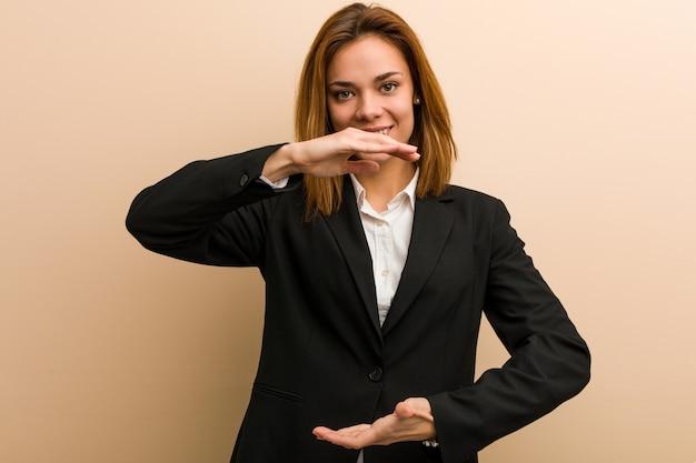 Junge kaukasische geschäftsfrau, die etwas mit beiden händen, produktdarstellung hält. Premium Fotos