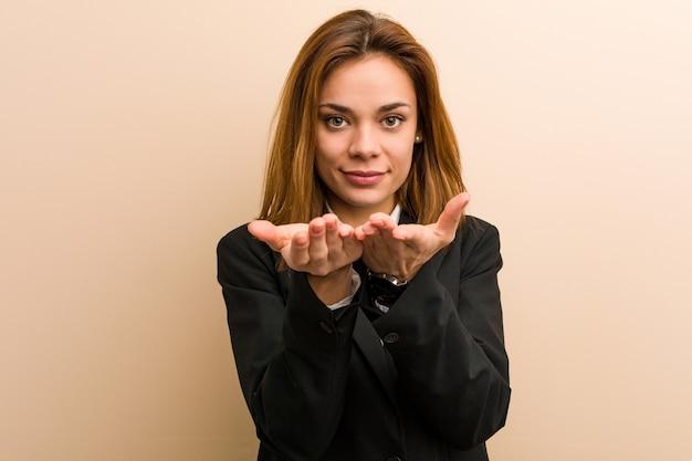Junge kaukasische geschäftsfrau, die etwas mit den palmen, kamera anbietend hält. Premium Fotos