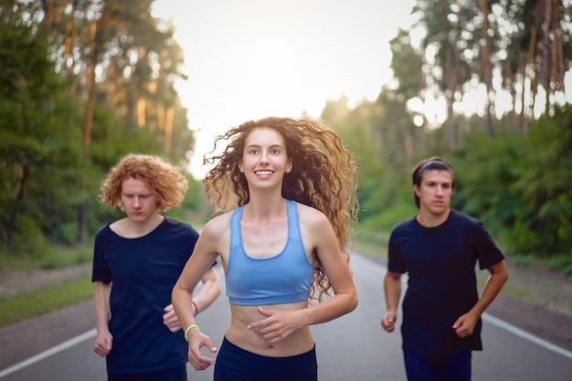 Junge kaukasische mann- und frauengruppe, die asphaltstraße läuft sonniger sommermorgen Premium Fotos