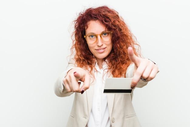 Junge kaukasische rothaarige frau, die ein fröhliches lächeln der kreditkarte hält, zeigt nach vorne. Premium Fotos