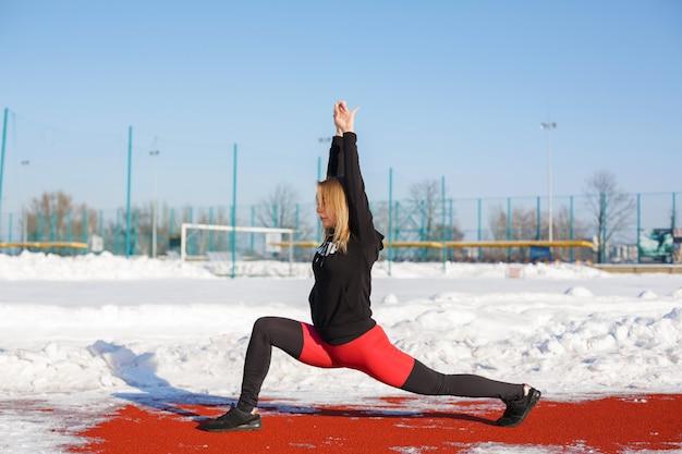 Junge kaukasische weibliche blondine in den violetten gamaschen, die übung auf einer roten laufbahn in einem schneebedeckten stadion ausdehnen. fit und sportlicher lebensstil Premium Fotos