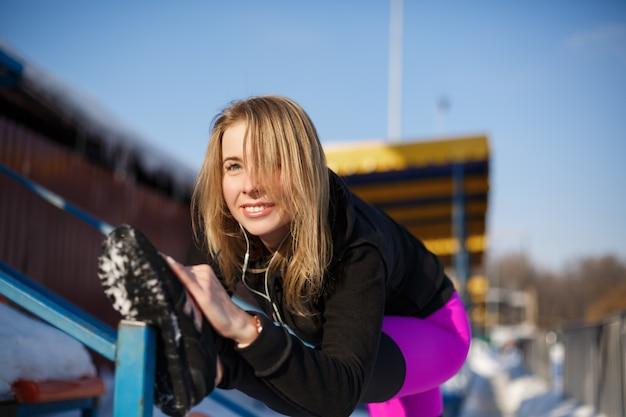 Junge kaukasische weibliche blondine in den violetten leggings, die übung auf tribüne auf einem verschneiten stadion strecken. fit und sportlicher lebensstil. Premium Fotos