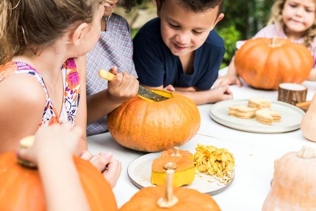 Junge kinder, die halloween jack-o-laternen schnitzen Kostenlose Fotos