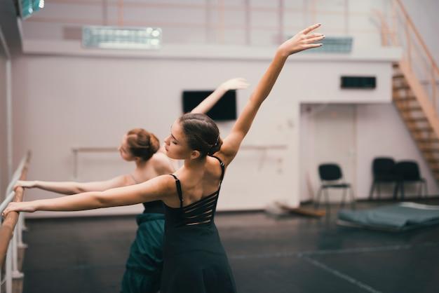 Junge klassische weibliche tänzer, die im tanzstudio üben Kostenlose Fotos