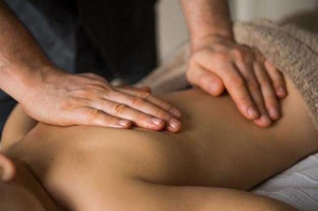 Junge kleinkind entspannt sich von einer therapeutischen massage. physiotherapeut arbeitet mit patienten in der klinik auf dem rücken eines kindes Premium Fotos