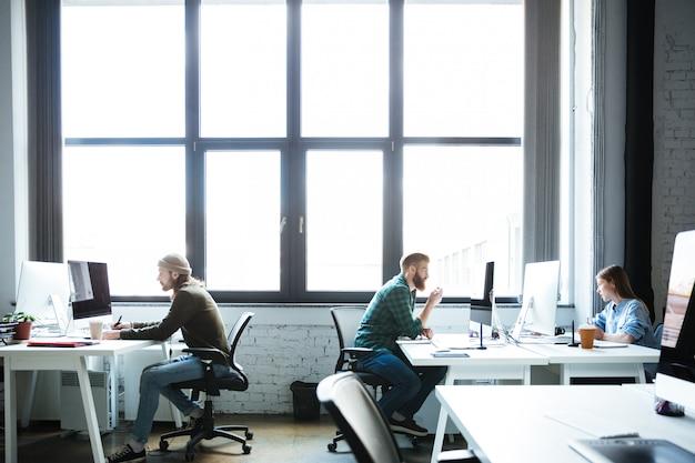 Junge kollegen arbeiten im büro mit computern Kostenlose Fotos