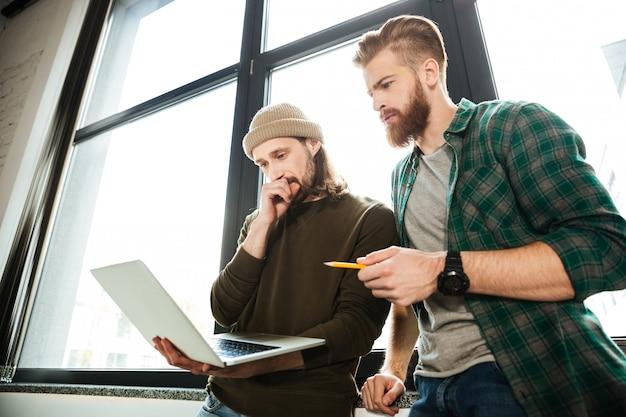 Junge konzentrierte männerkollegen im büro mit laptop Kostenlose Fotos