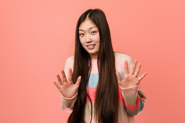 Junge kühle chinesische frau, die jemand zeigt eine geste des ekels zurückweist. Premium Fotos