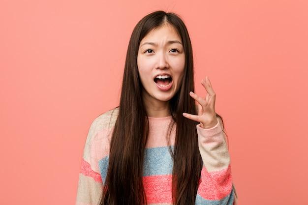 Junge kühle chinesische frau, die mit raserei schreit. Premium Fotos