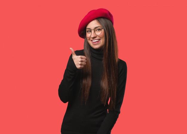 Junge künstlerfrau, die oben daumen lächelt und anhebt Premium Fotos