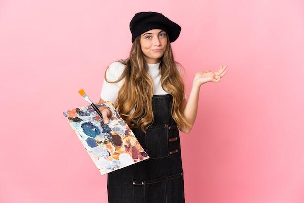 Junge künstlerin, die eine palette auf rosa hält, die zweifel beim erhöhen der hände hat Premium Fotos