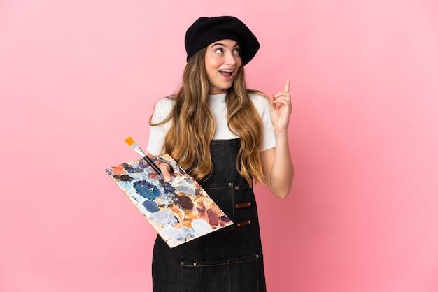 Junge künstlerin, die eine palette auf rosa hält und eine idee denkt, die den finger nach oben zeigt Premium Fotos