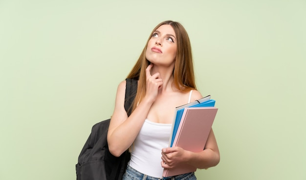 Junge kursteilnehmerfrau über getrenntem grünem hintergrund eine idee denkend Premium Fotos