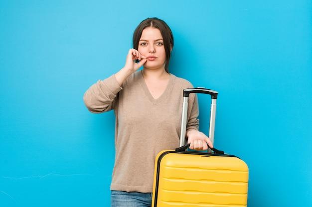 Junge kurvige frau, die einen koffer mit den fingern auf den lippen hält, die ein geheimnis halten. Premium Fotos