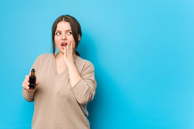 Junge kurvige frau, die einen verdampfer hält, sagt eine geheime heiße bremsnachricht und schaut zur seite Premium Fotos