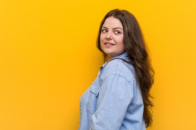 Junge kurvige plusgrößenfrau schaut beiseite lächelnd, fröhlich und angenehm. Premium Fotos