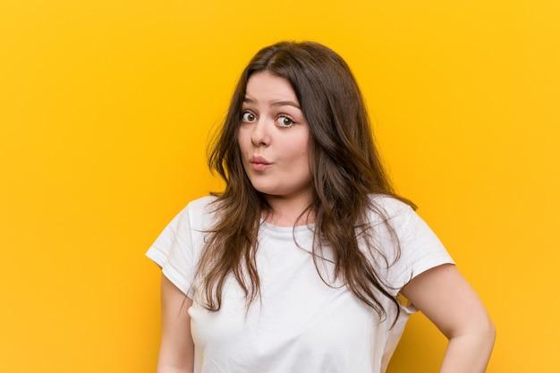 Junge kurvige plusgrößenfrau zuckt verwirrt mit den schultern und den offenen augen. Premium Fotos