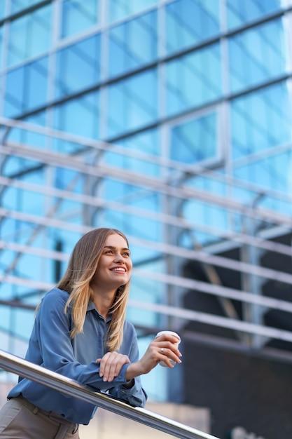 Junge lächelnde berufstätige frau, die eine kaffeepause während ihres vollen arbeitstages hat. sie hält einen pappbecher im freien in der nähe des geschäftsgebäudes, während sie sich entspannt und ihr getränk genießt. Kostenlose Fotos