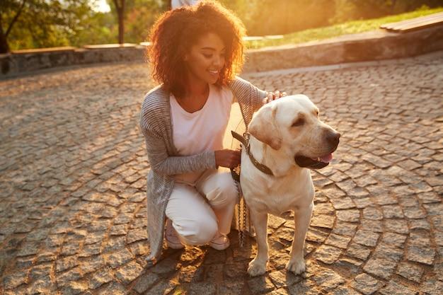 Junge lächelnde dame in der freizeitkleidung, die hund im park sitzt und umarmt Kostenlose Fotos