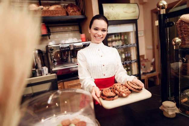 Junge lächelnde frau, die mit rolls in der bäckerei steht Premium Fotos