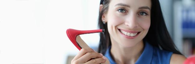 Junge lächelnde frau, die rote hochhackige sandalen in den