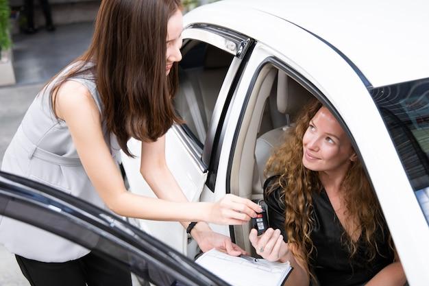 Junge lächelnde frau, die schlüssel eines neuen autos erhält. Premium Fotos