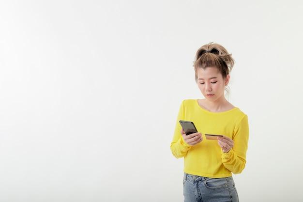 Junge lächelnde frau, die telefon und nummer der kreditkarte verwendet, um online einzukaufen Premium Fotos