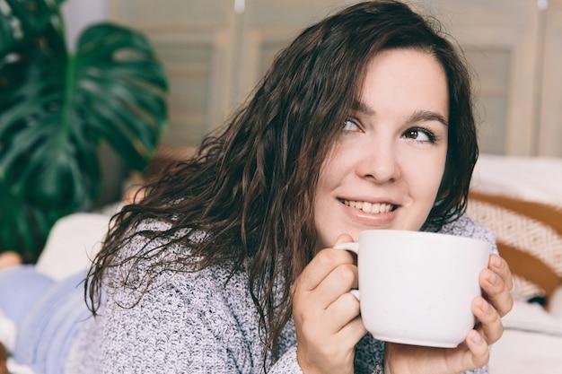 Junge lächelnde frau im grauen lügen auf dem bett mit weißer schale. Premium Fotos