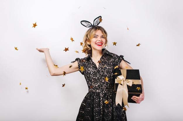 Junge lächelnde frau mit geschenkbox, die helles ereignis, geburtstagsfeier feiert, trägt elegantes schwarzes modekleid. funkelndes goldkonfetti, spaß haben, tanzen. Kostenlose Fotos