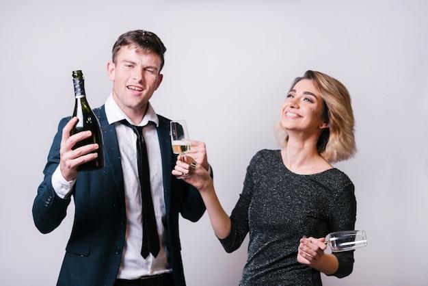 Junge lächelnde frau mit gläsern nähern sich mann mit flasche getränk Kostenlose Fotos